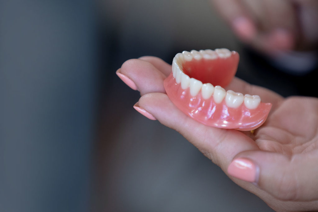 woman holding denture Select Dental